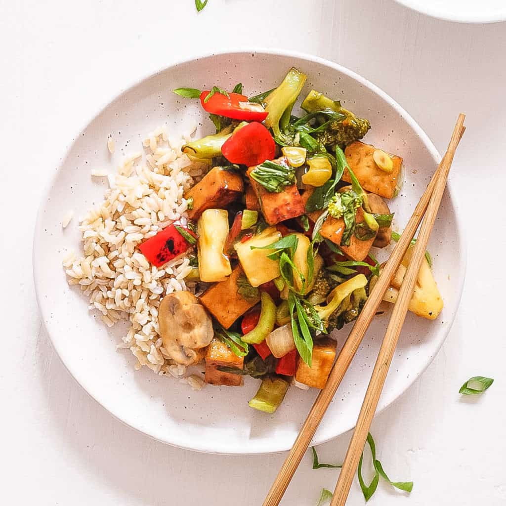 sweet and sour tofu with veggies, served on a white plate with chopsticks