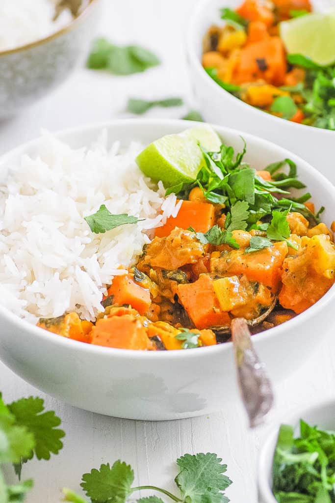 sweet potato and chickpea curry in a white bowl served with rice