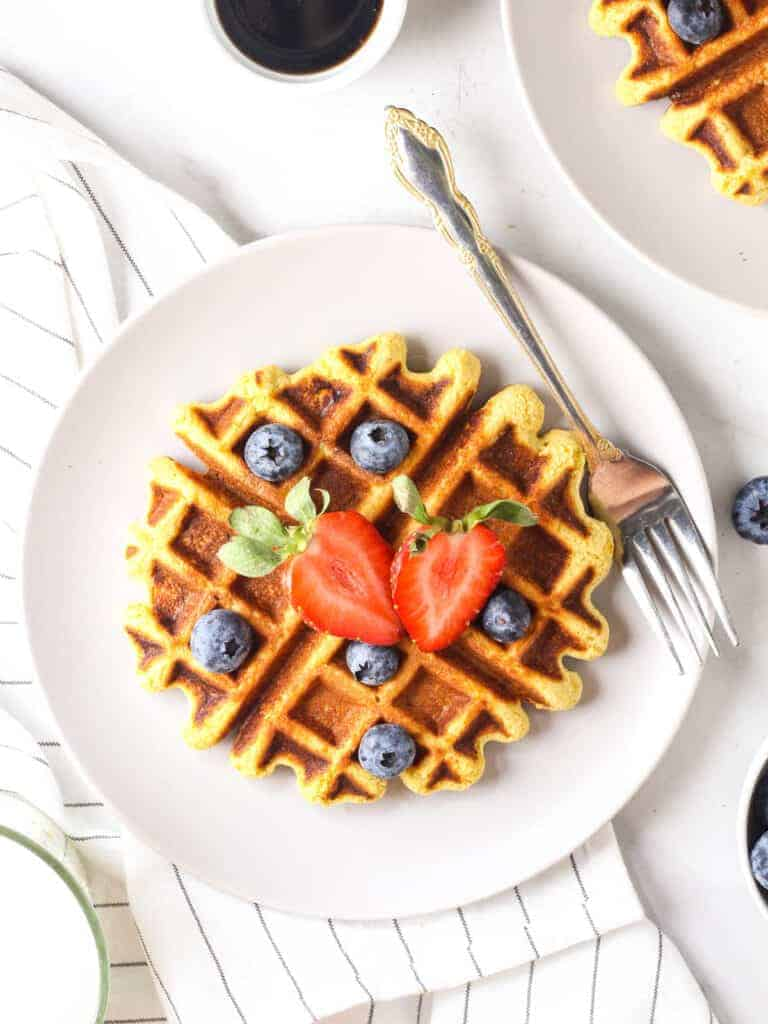 chickpea waffles topped with blueberries and strawberries - high protein vegan breakfast