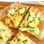 zucchini flatbread pizza with fresh corn and cheese on wood serving board