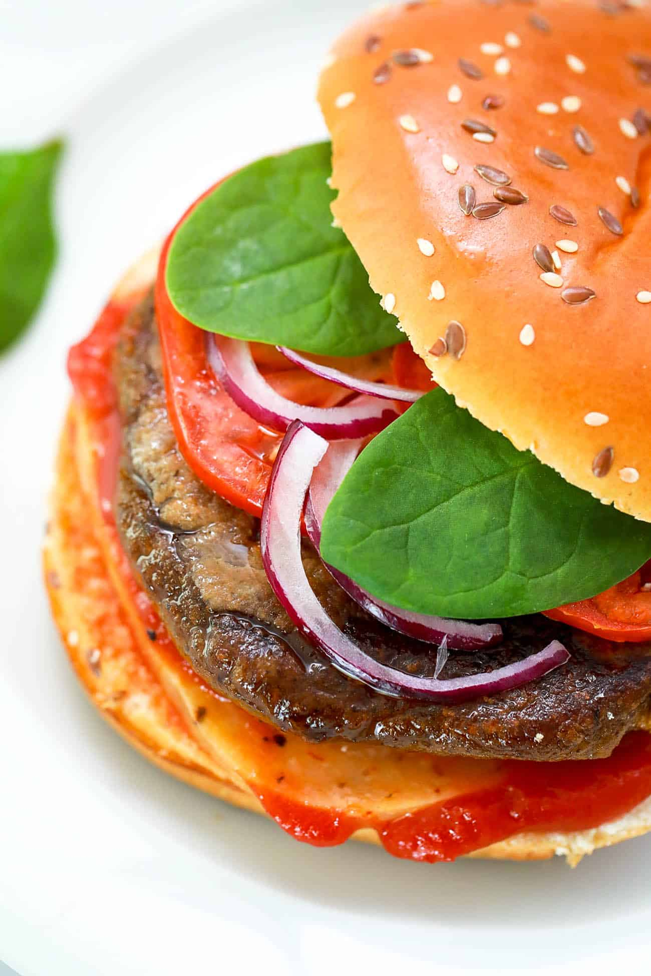 pumpkin burgers on a white plate - black bean pumpkin burgers topped with spinach, tomato, cheese, onions, ketchup
