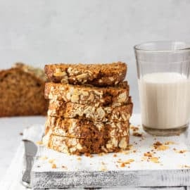 vegan banana bread recipe without butter served on a grey cutting board with a glass of milk