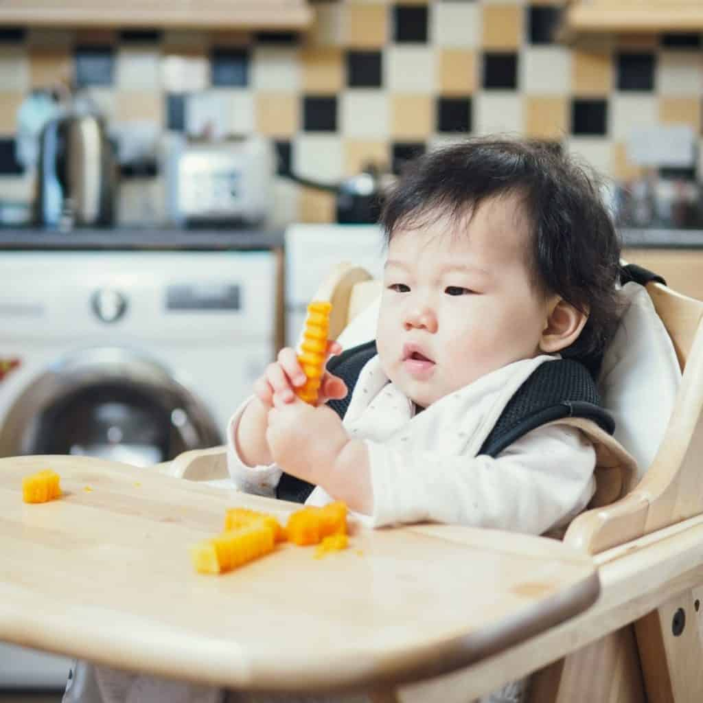 baby in high chair eating sliced butternut squash bites