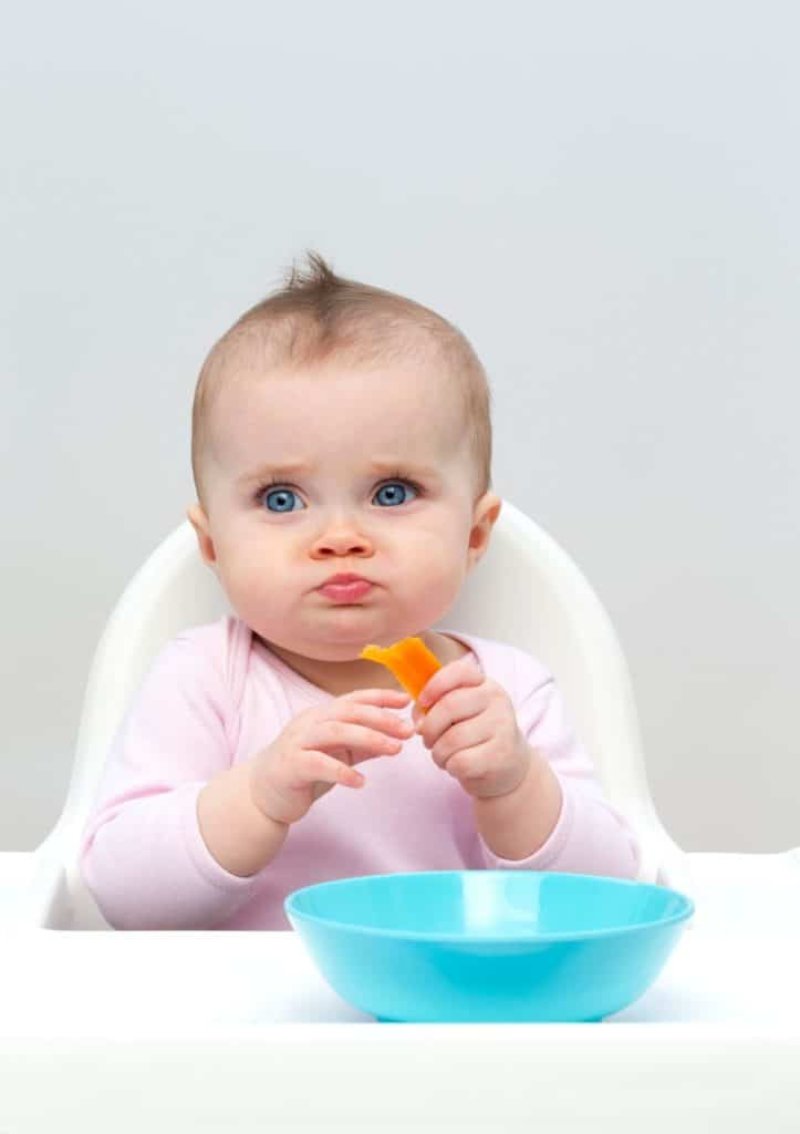 baby in high chair with blue bowl in front of her holding butternut squash bites