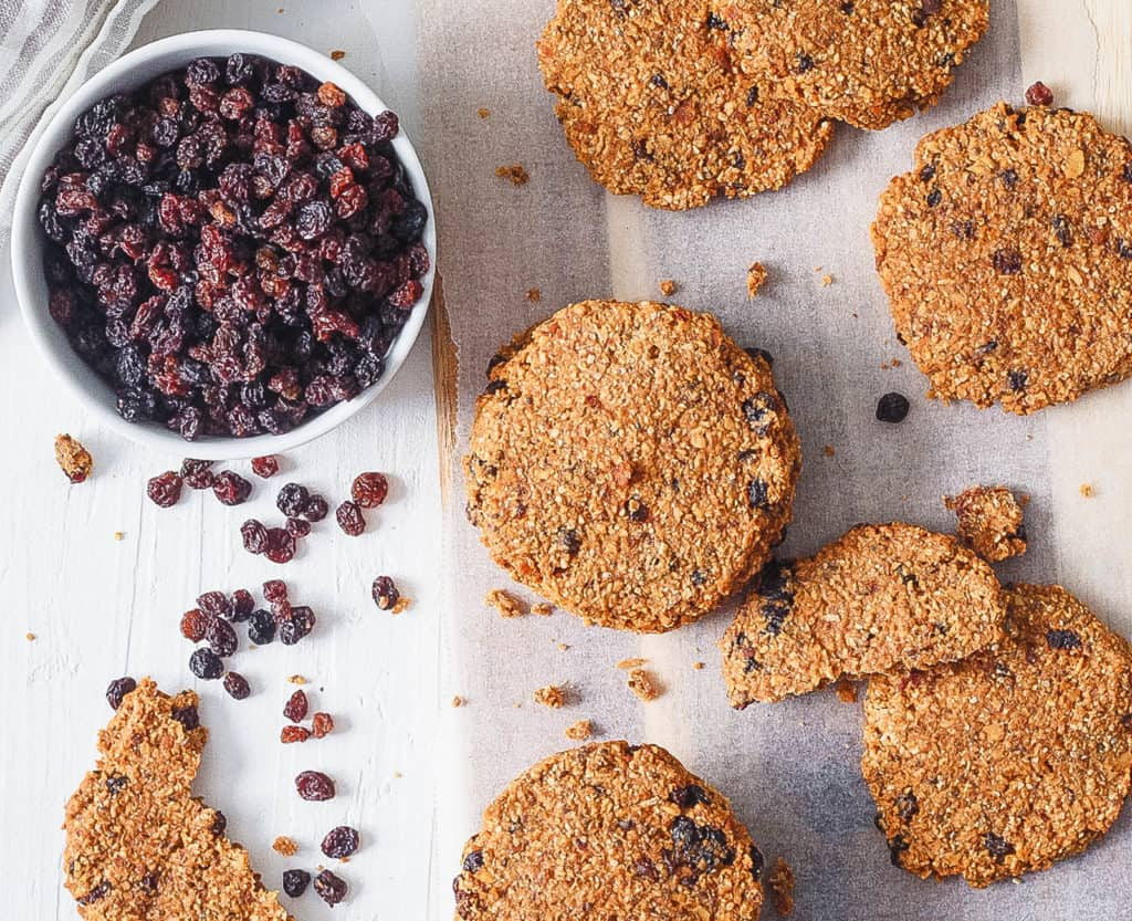 healthy oatmeal raisin cookies stacked on parchment paper