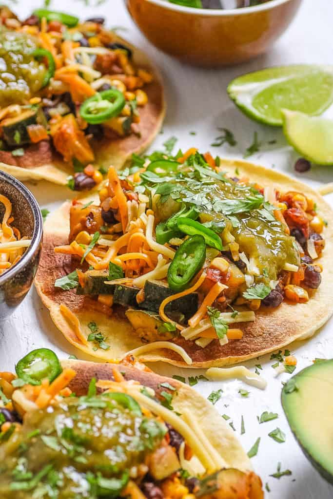 healthy vegetarian black bean tostadas served on a white cutting board, topped with cheese and tomatillo salsa