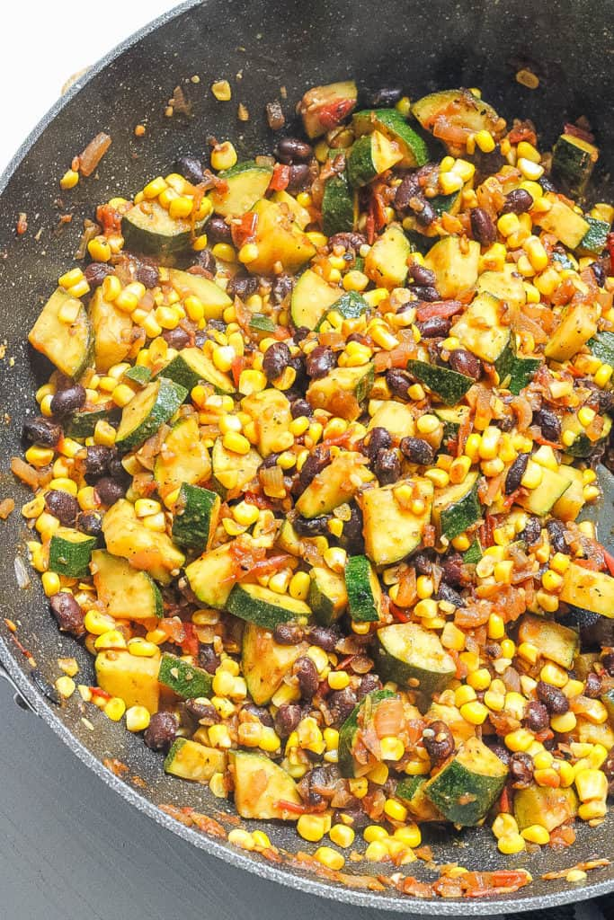 corn and zucchini mixture sauteeing in a pan