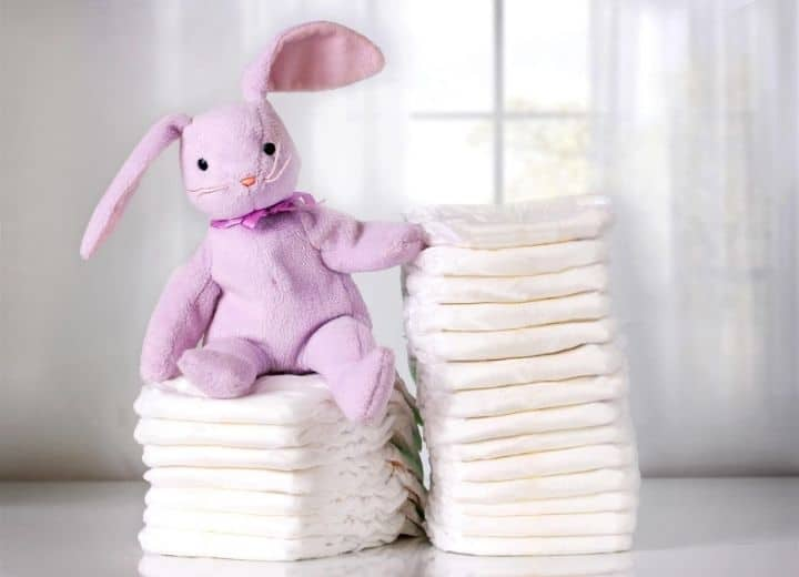 two stacks of white diapers with a stuffed purple rabbit on top