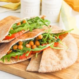 pita sandwich with chickpeas, arugula, tomato, and yogurt sauce served on a wooden cutting board