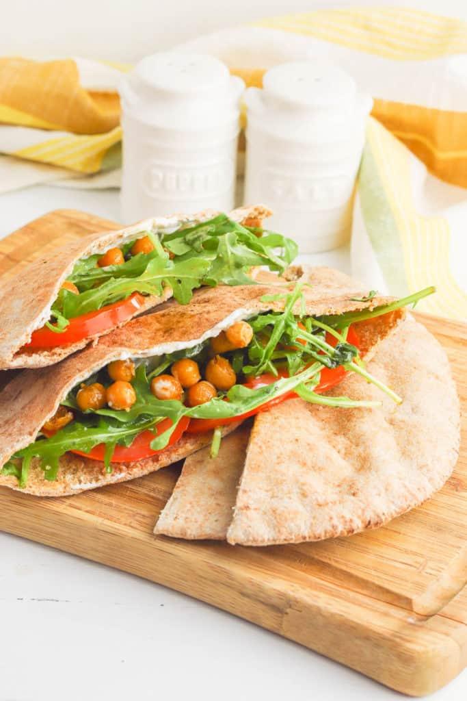 pita sandwich with chickpeas, arugula, tomato, and yogurt sauce served on a wooden cutting board