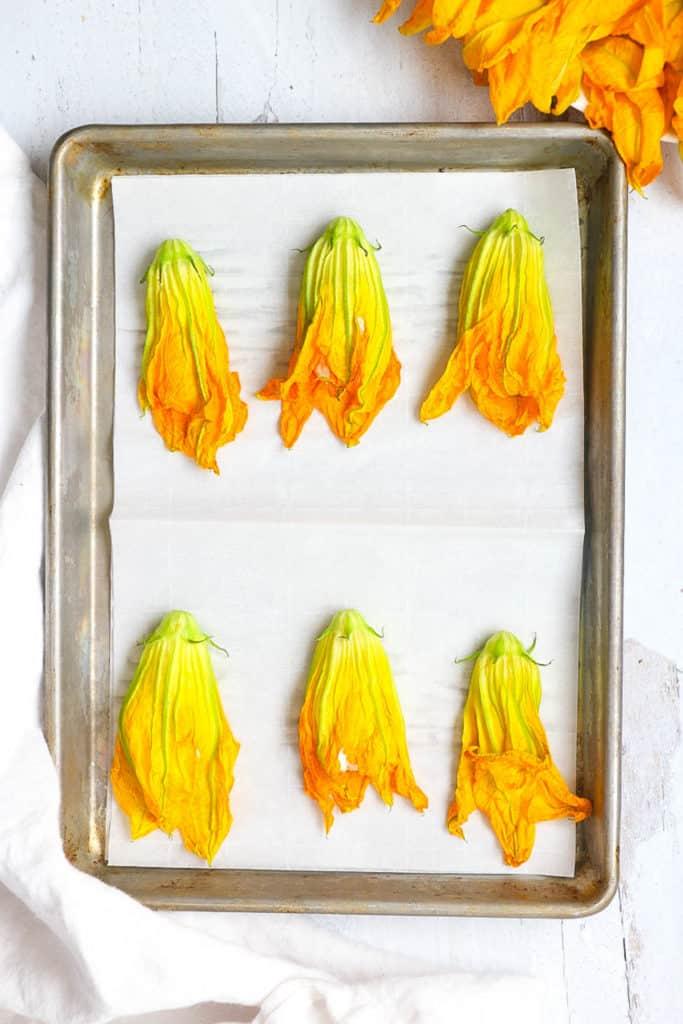 stuffed zucchini flowers on a baking sheet