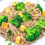 tofu and broccoli stir fry with sesame noodles on a white plate