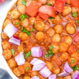 trader joe's channa masala recipe topped with tomatoes and onions, served in a white bowl