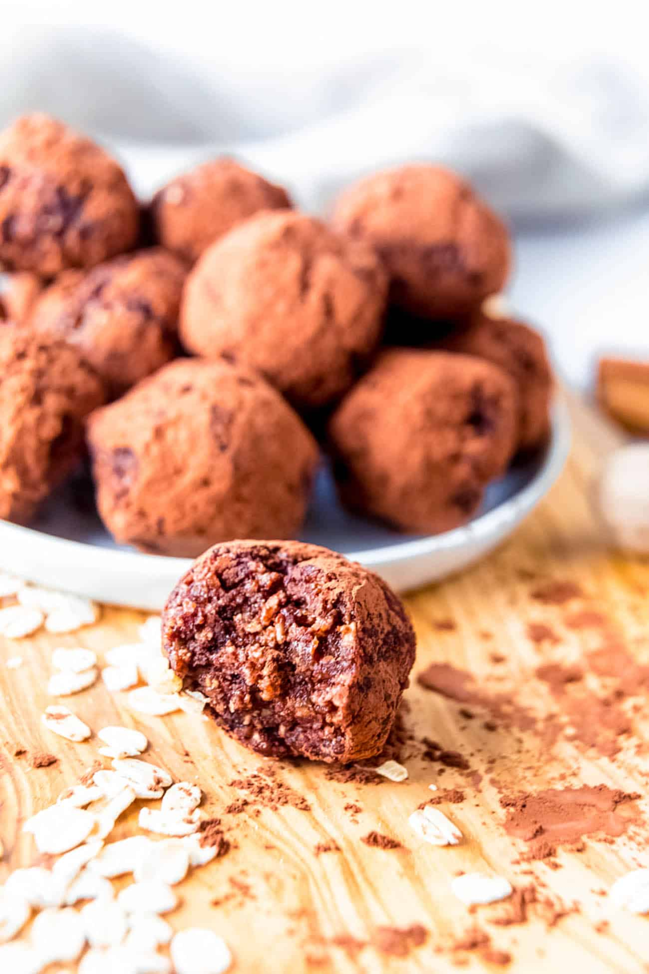 date balls on a white platter with a bite taken out of a ball