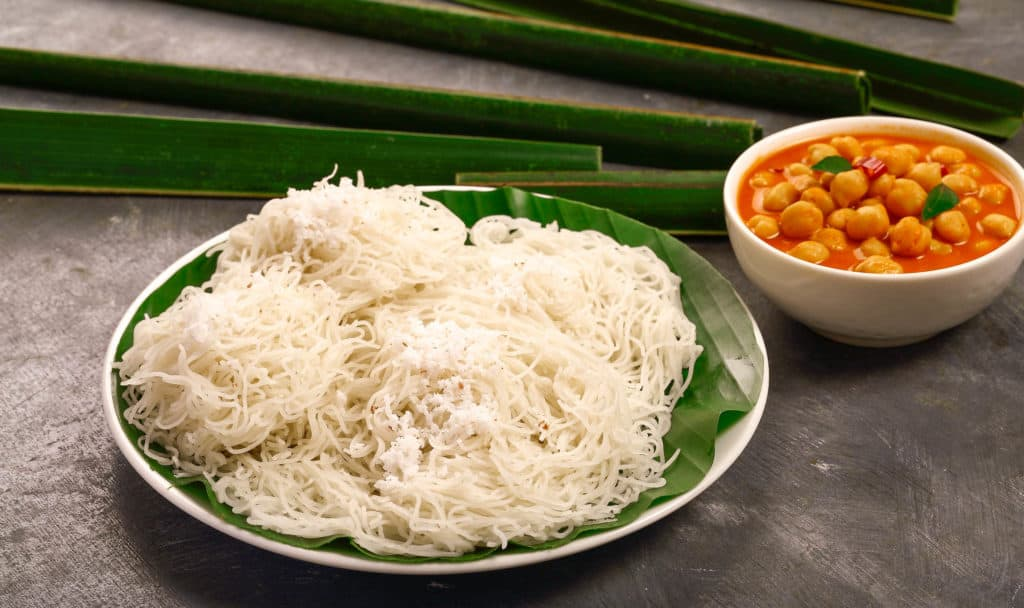 Steamed rice noodles, idiappam with chickpea curry- Vegetarian Kerala foods background.
