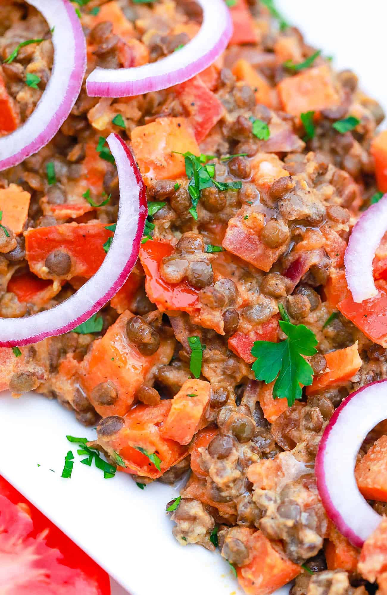 Instant Pot Lentils served with red onions and cilantro on a white plate