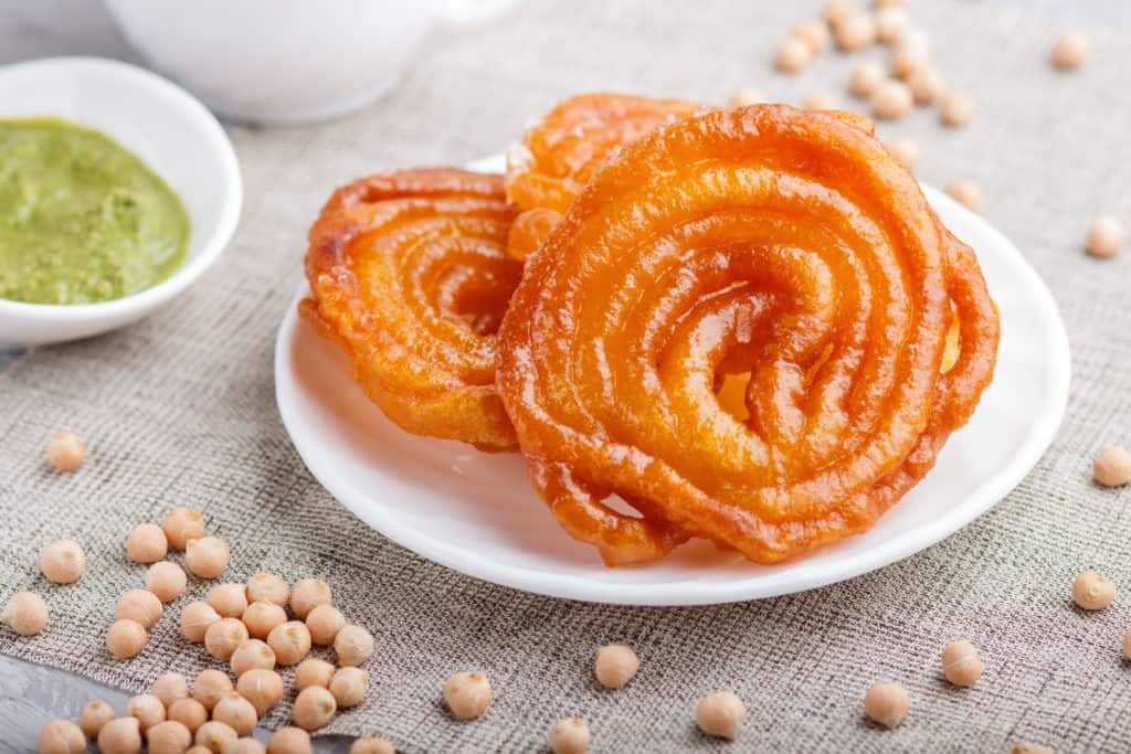 traditional indian candy jalebi/Imarti in white plate with mint chutney on a gray concrete background. side view, close up.