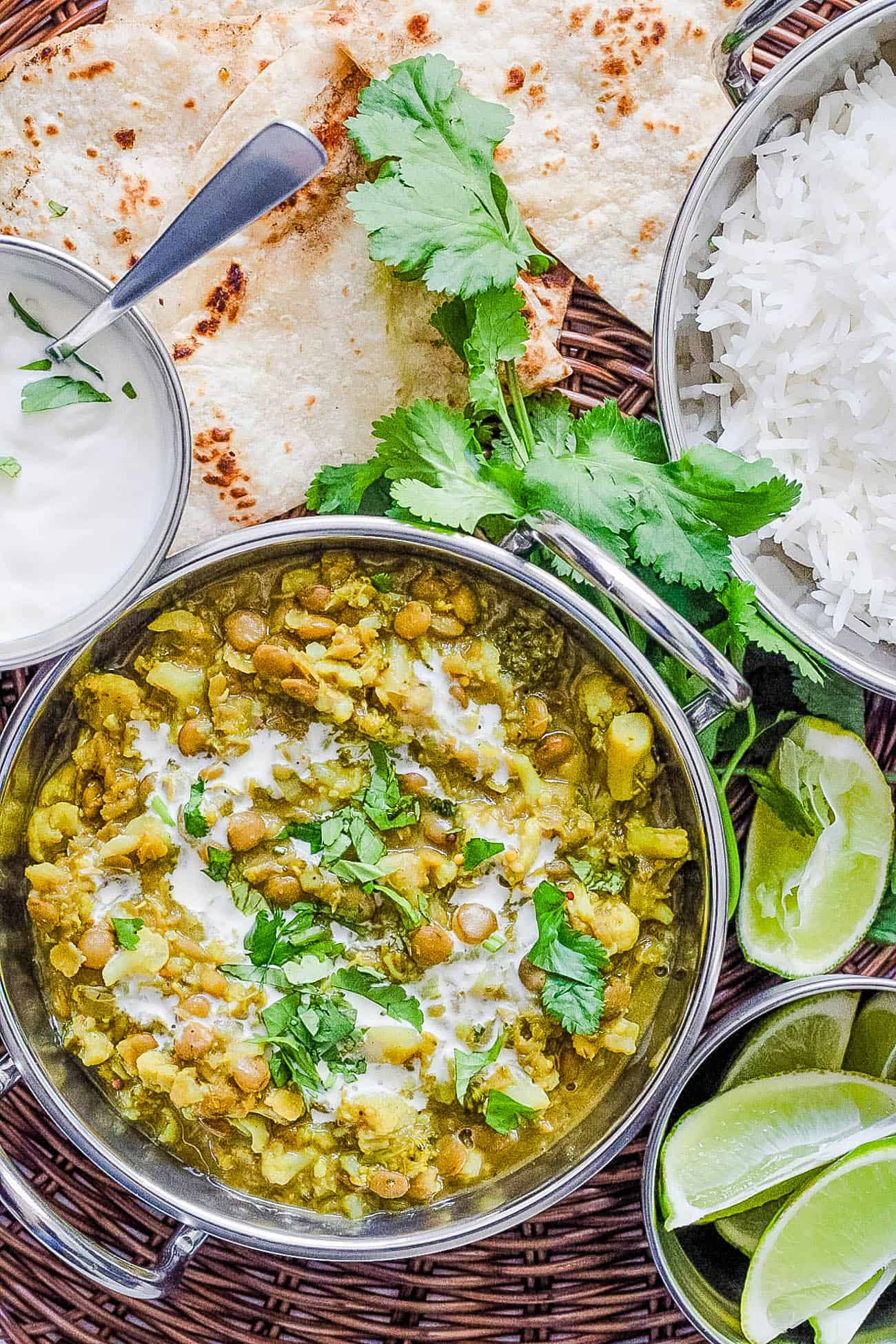Lentil Cauilflower Curry served in a stainless steel pot with naan, cilantro and rice on the side