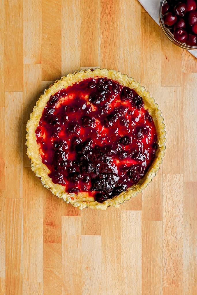 cherry preserves spread on pie crust