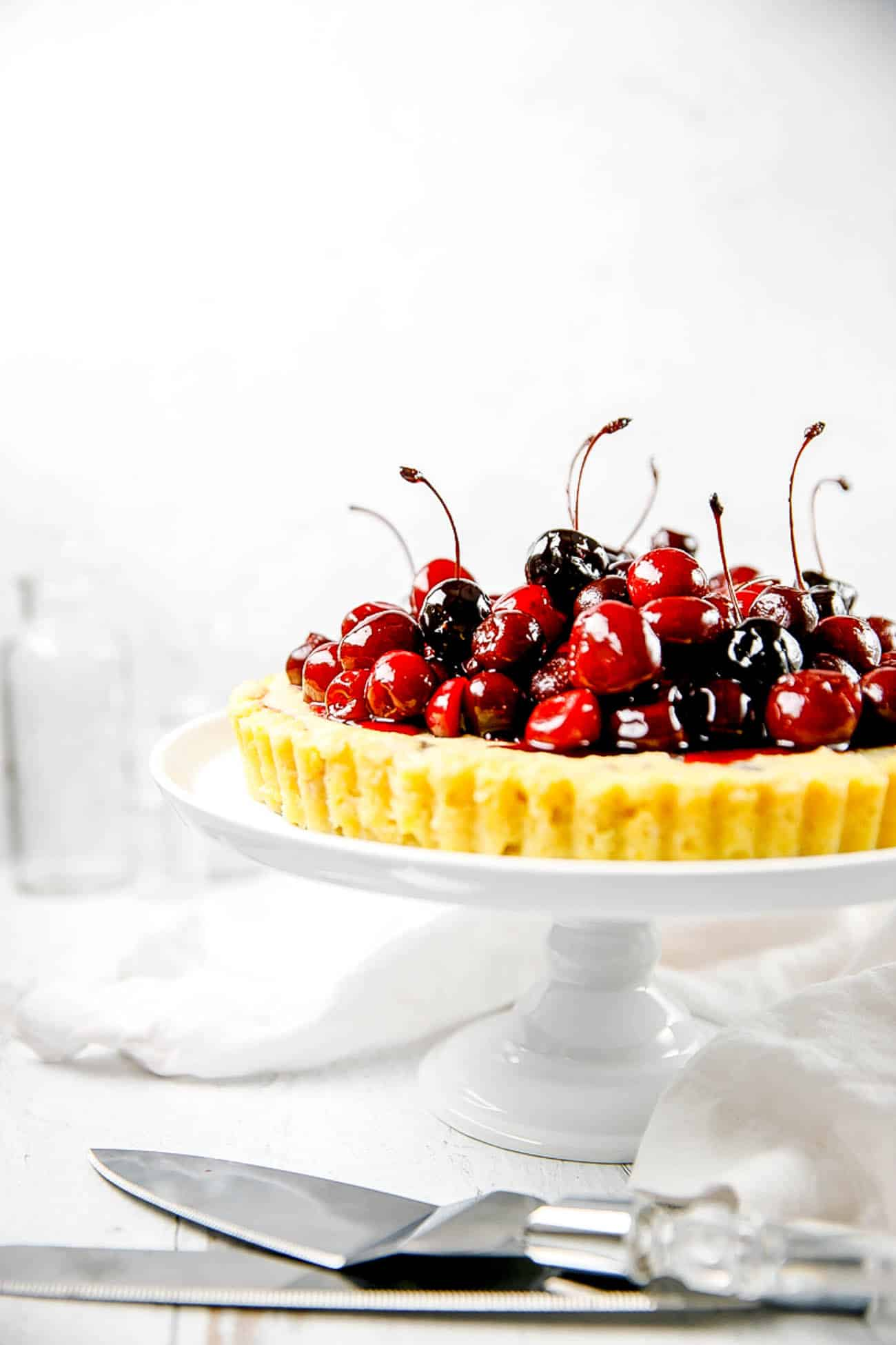 dark chocolate and ricotta pie, finished with fresh cherries, on a cake stand
