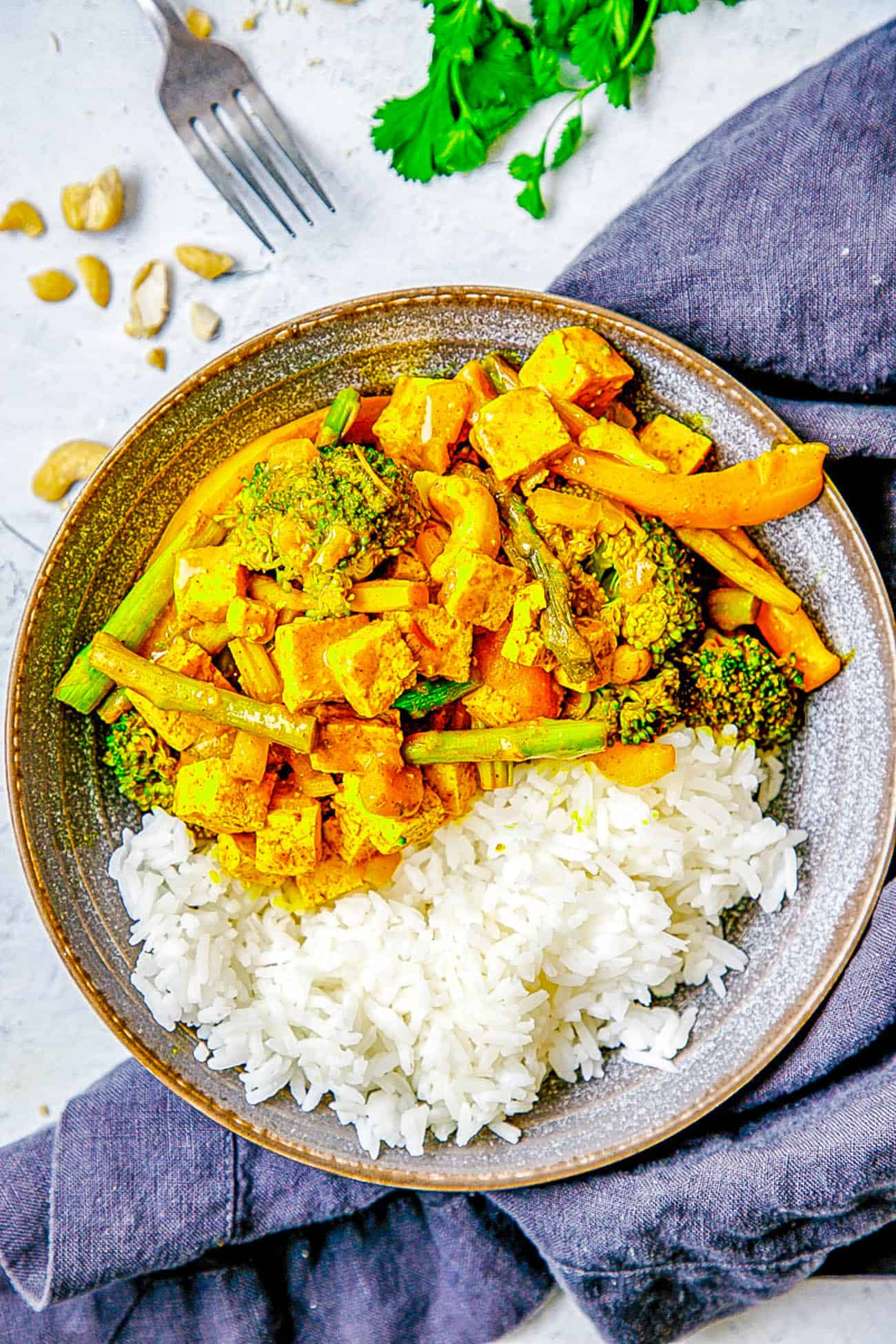 Tofu Yellow Curry with Veggies and Cashews served in a grey bowl with white rice