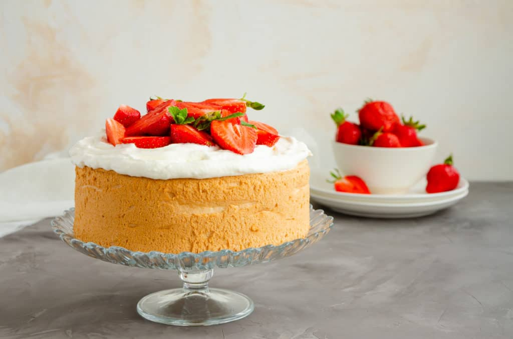 Angel food cake with whipped cream and slices of fresh strawberries on top on a concrete background. Summer dessert. Horizontal orientation, copy space - foods that start with a