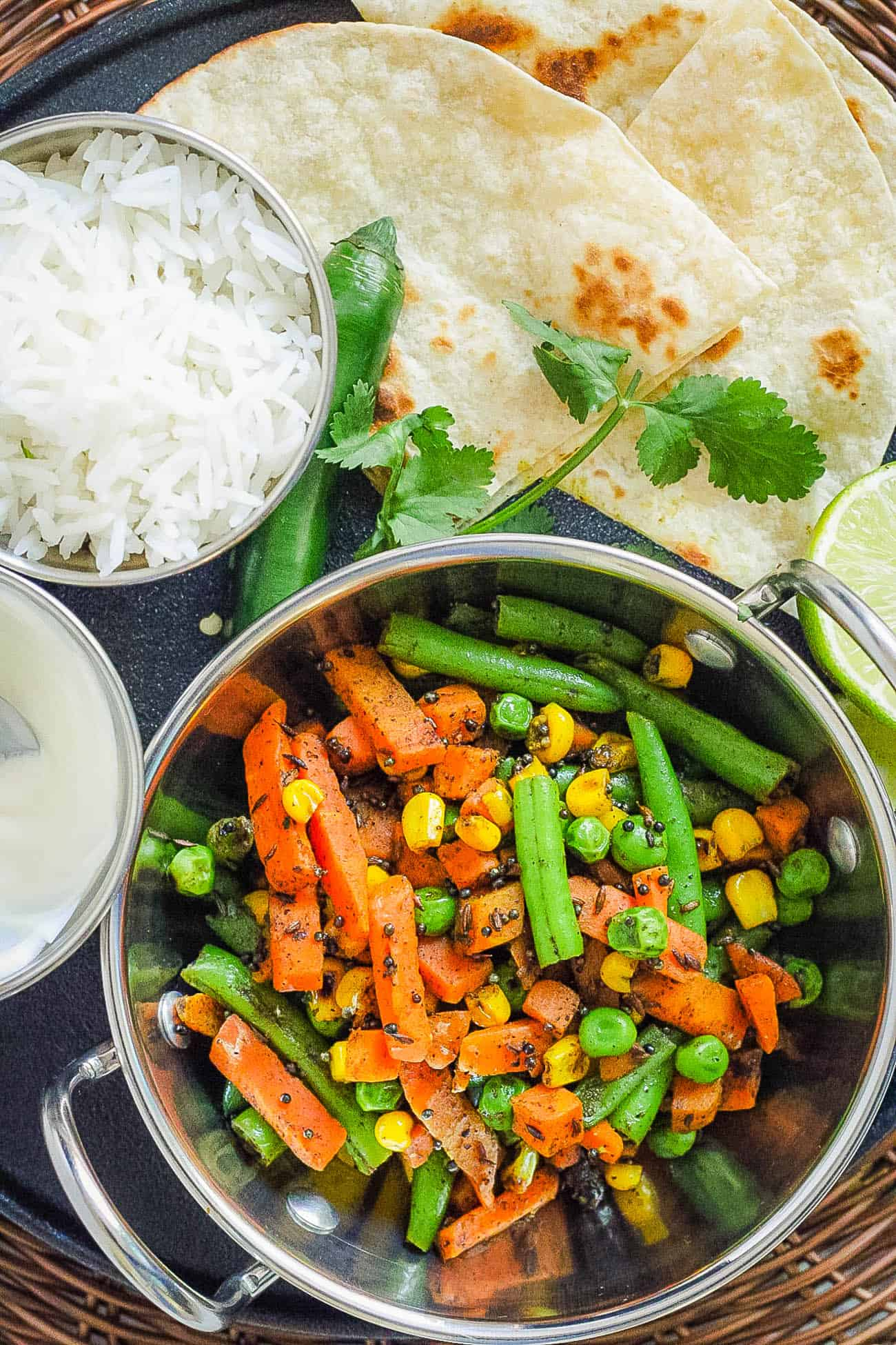 indian vegetables served in a stainless steel pot with naan and rice on the side