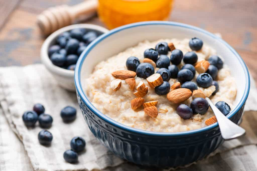 Oatmeal with blueberries and almonds in blue ceramic bowl on a wooden table.