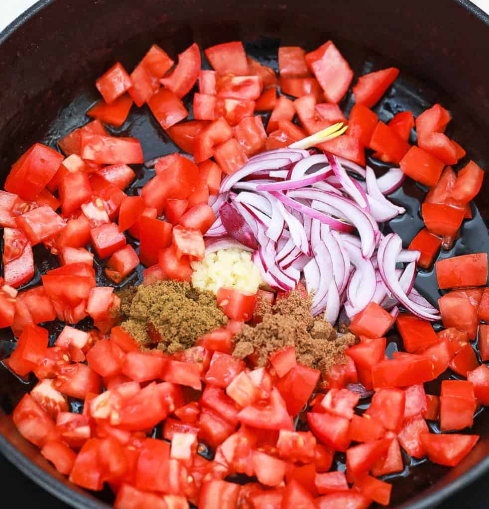 tomatoes onions and spices added to skillet