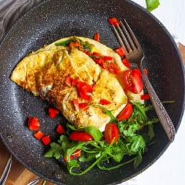 low calorie omelette with indian spices and veggies served on a black plate - healthy omelette
