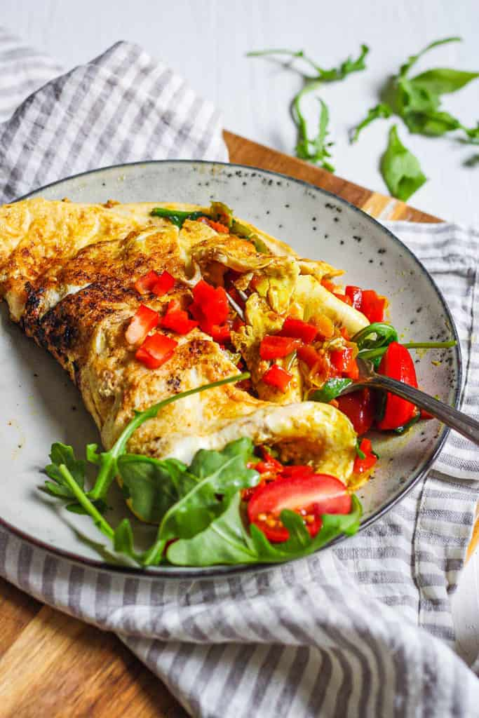 low calorie omelette with indian spices and veggies served on a grey plate