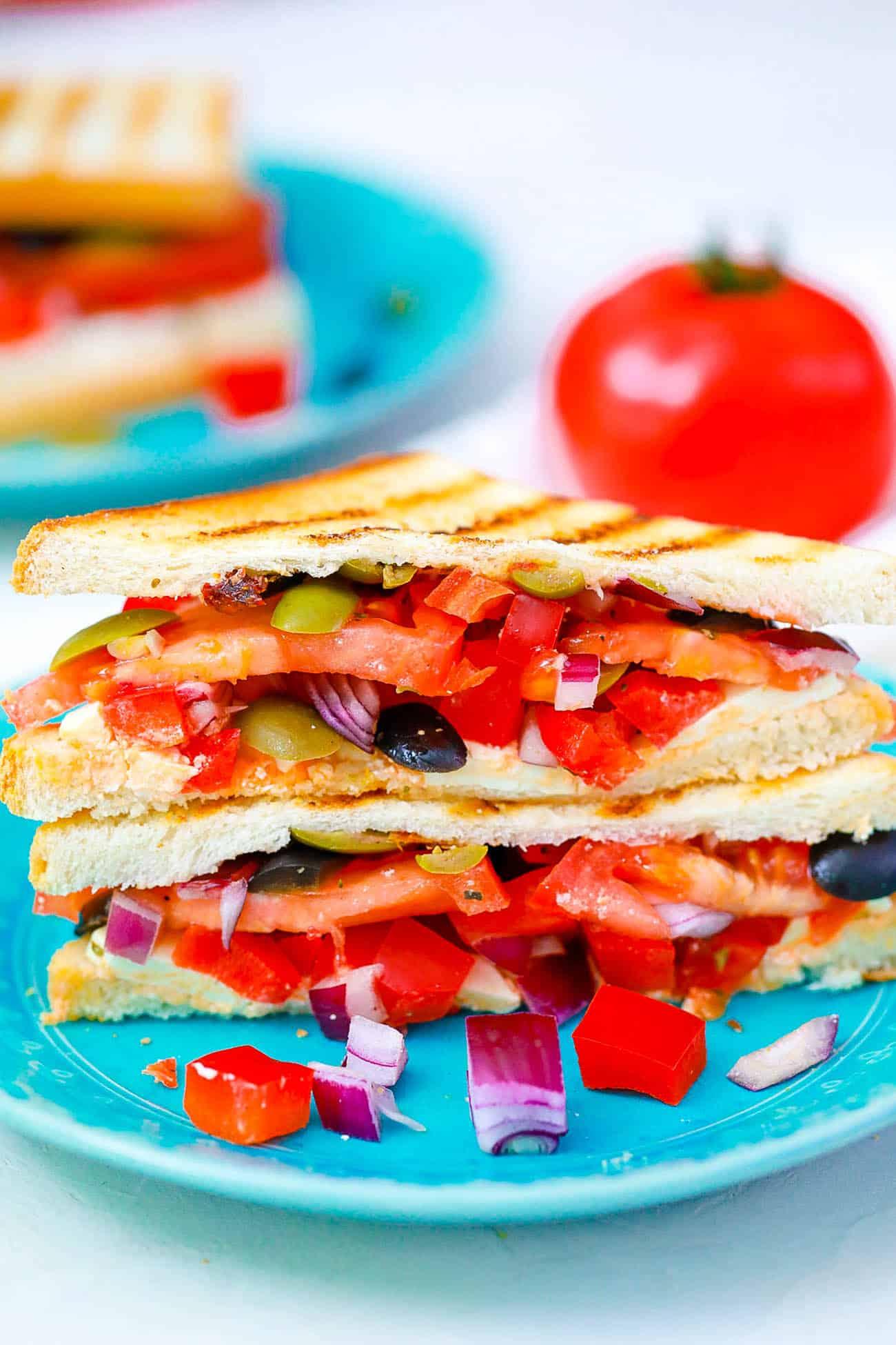 mediterranean sandwich cut in half on a blue plate