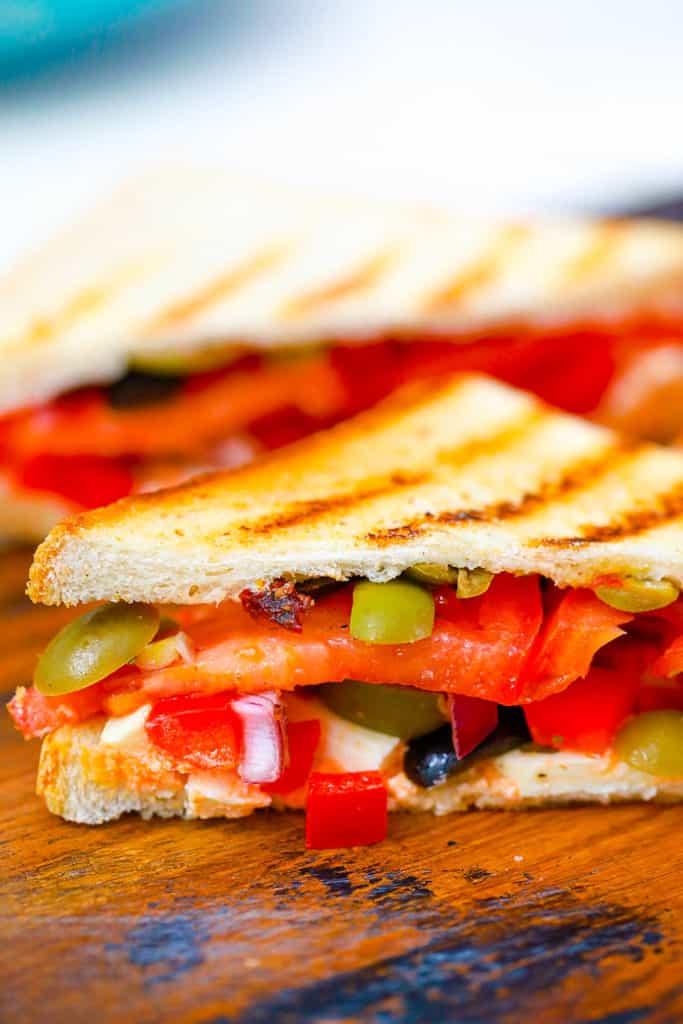 mediterranean sandwich cut in half on a wooden cutting board