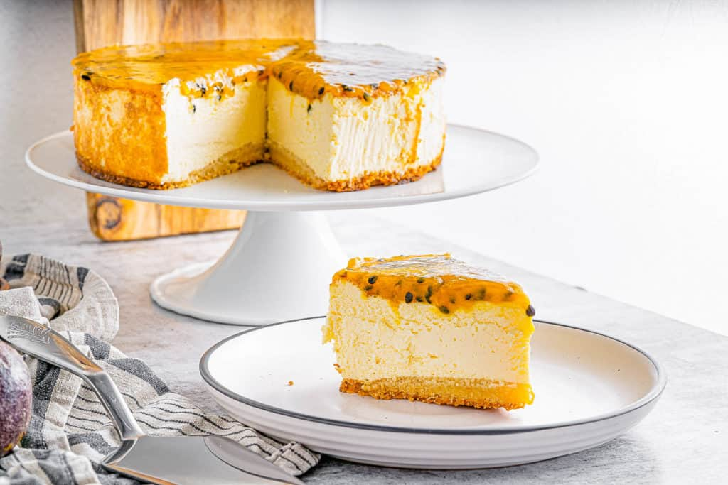 slice of passionfruit cheesecake on a plate with whole cheesecake in the background