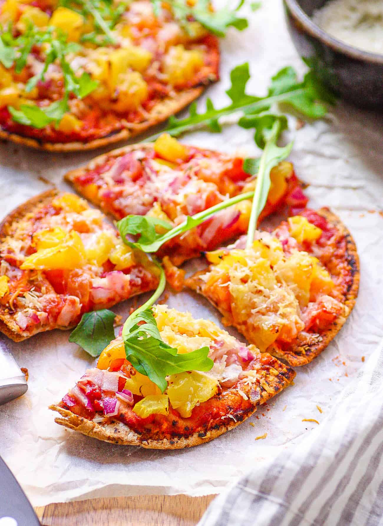 healthy homemade pita pizza / pita bread pizza with veggies as toppings on a cutting board