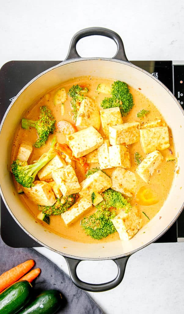 veggies added to coconut milk in a pan