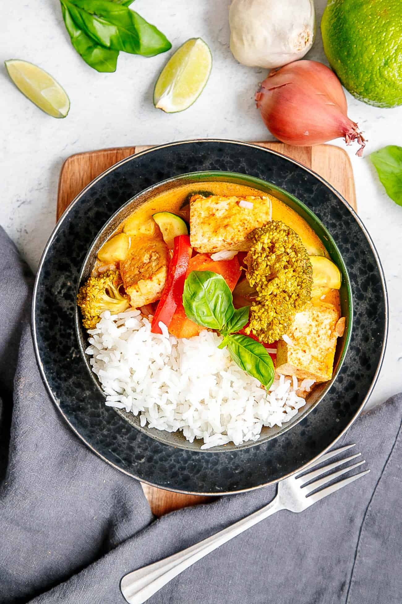 vegan panang curry in a black bowl with fresh herbs and rice