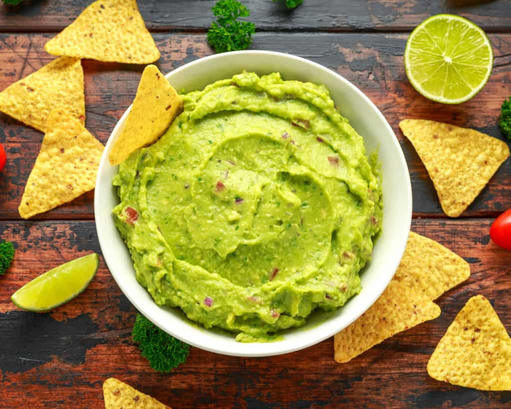 vegan guacamole with tortilla chips in a white bowl