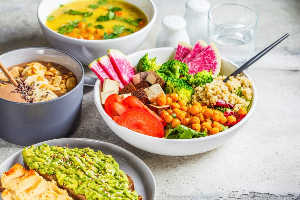 vegan lunch ideas - Vegan lunch table. Chocolate smoothie bowl, Buddha bowl with tofu, chickpeas and quinoa, lentil soup and toasts on a gray background.