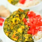 vegan palak paneer served with tomatoes and rice in a white bowl