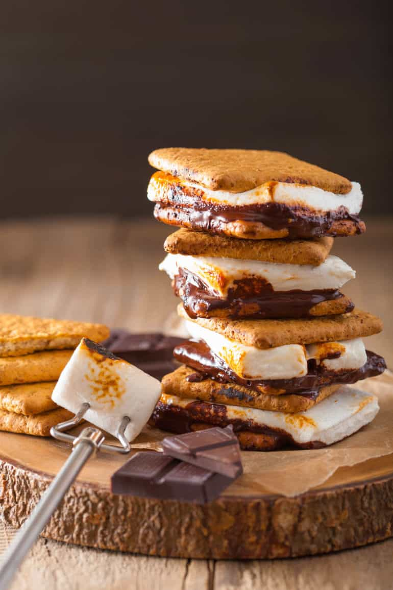 vegan smores stacked on top of a wooden cutting board