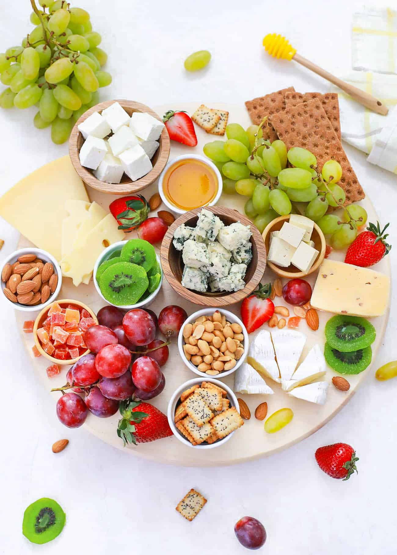 vegetarian cheese board served on a wooden platter with cheeses, fruits, nuts, condiments, crackers