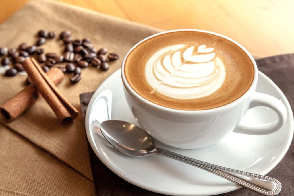 foods that start with c - Cup of cappuccino with coffee beans and cinnamon sticks