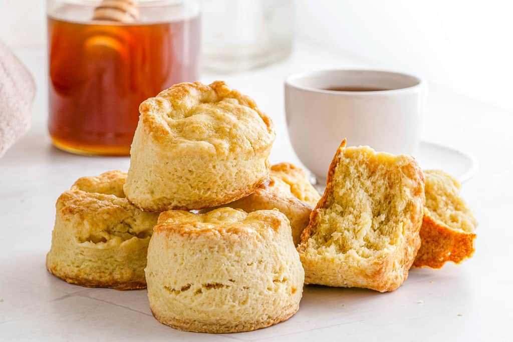Easy Biscuit Recipe without Baking Powder - biscuits stacked in a bowl and on top of each other served with tea and honey