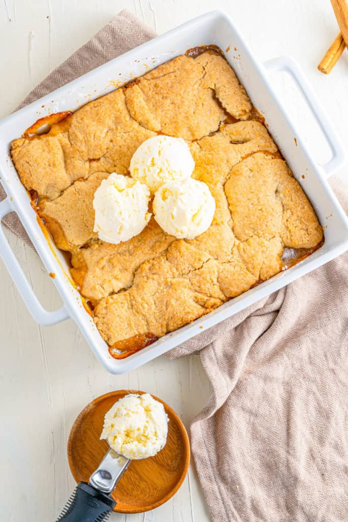 Vegan Peach Cobbler in a baking dish topped with ice cream