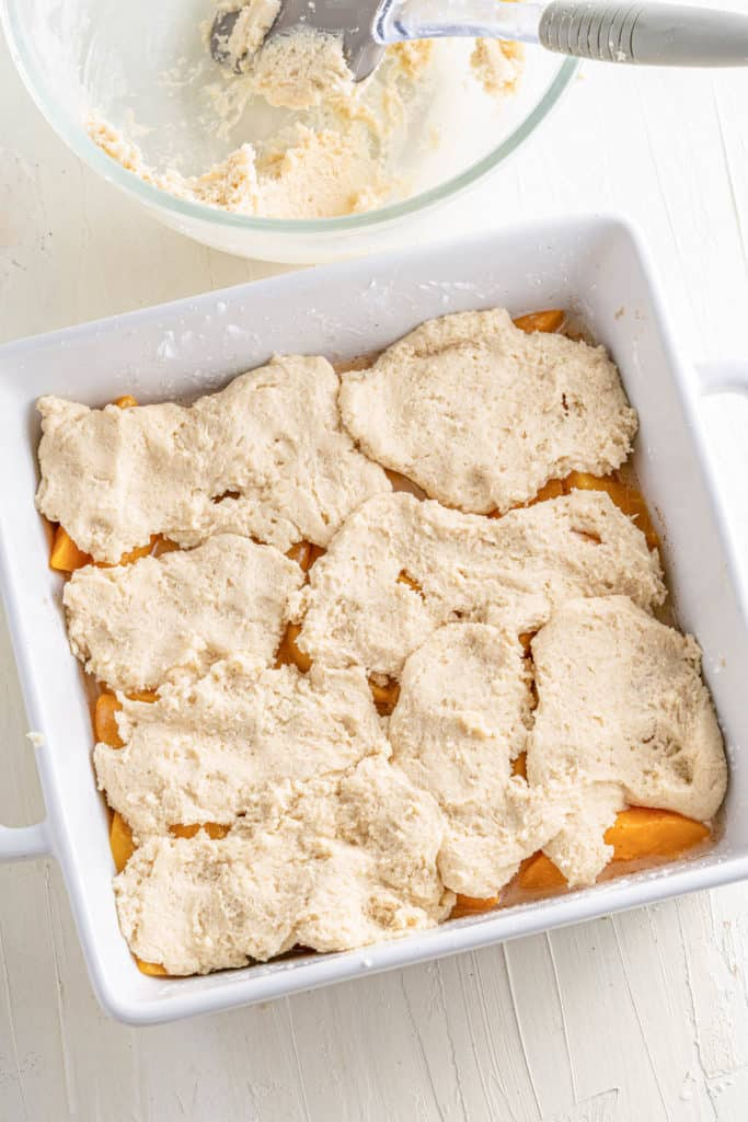 cobbler topping added to peaches in a baking dish