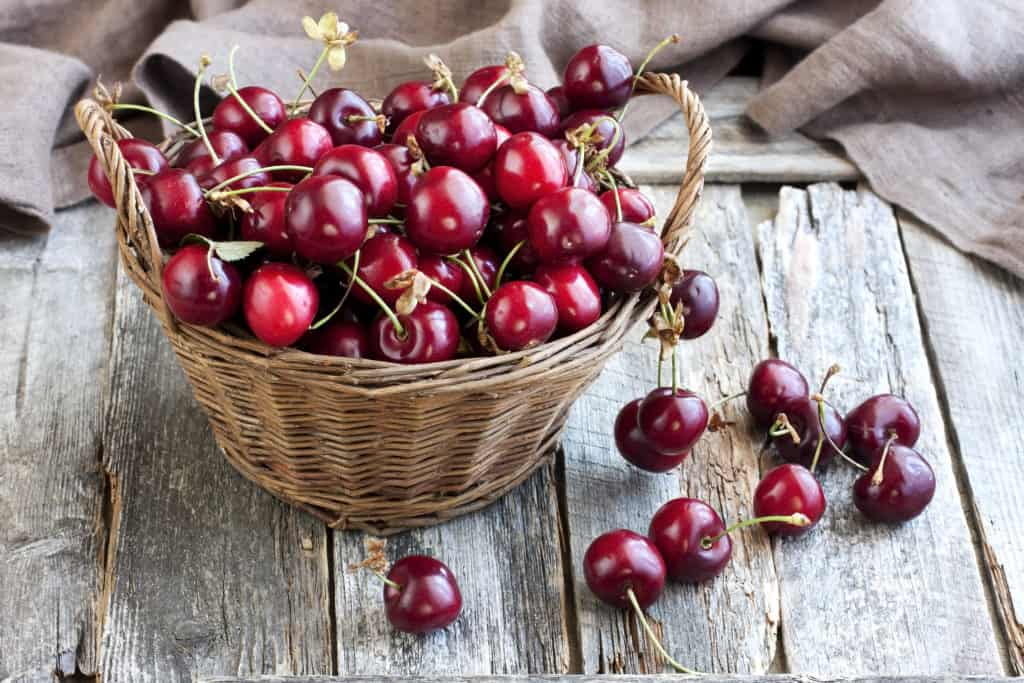 Wicker basket with cherries on wooden background - foods that start with c