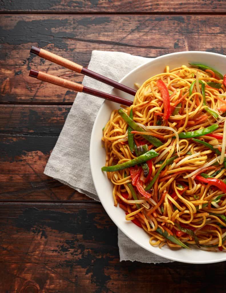 foods that start with c - Chow mein, noodles and vegetables dish with wooden chopsticks