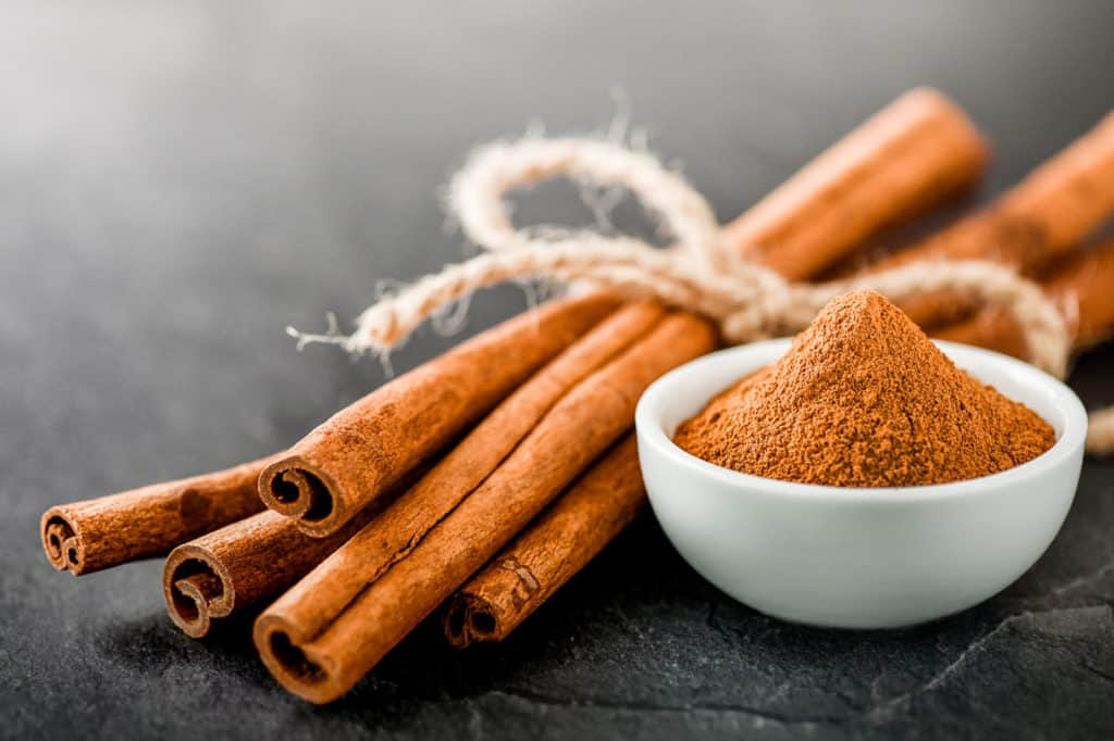 foods that start with c - Cinnamons dried sticks on dark stone table. Cinnamon ginger powder in white bowl on black board.