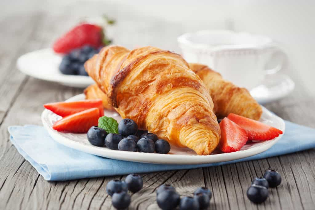 Delicious breakfast with fresh croissants and ripe berries on old wooden background